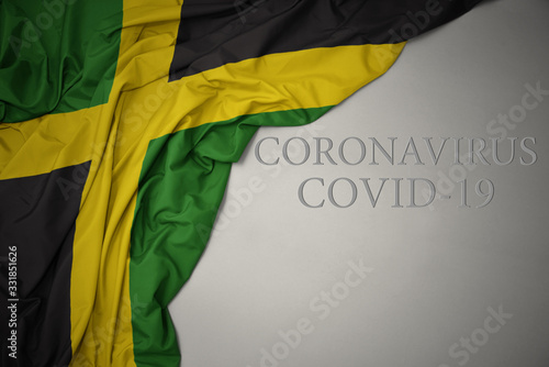 Photo waving national flag of jamaica on a gray background with text coronavirus covid-19