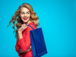canvas print picture Cheerful  young woman holds bags with a purchases. Joyful trendy girl with a colorful shopping bags. Model in a red shirt over blue background holding bags with gifts. Happy caucasian woman.