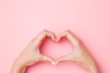 Heart Shape Created From Young Woman Hands On Pastel Pink Table Background. Love And Happiness Concept. Closeup. Top Down View. Point Of View Shot.