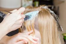 Hairdresser Hands Using Brush And Bleaching Strands Of Blonde Woman Hair. Beauty Salon. Closeup.