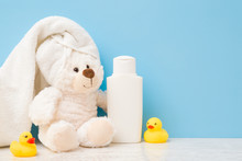 Smiling, Lovely White Teddy Bear Sitting With Towel On Head. Yellow Rubber Ducks And Shampoo Bottle On Shelf. Children Bathing Concept. Empty Place For Text On Light Blue Wall. Pastel Color. Closeup.