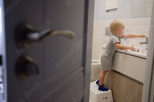 Little blond boy learning brushing his teeth in bath Fototapeta