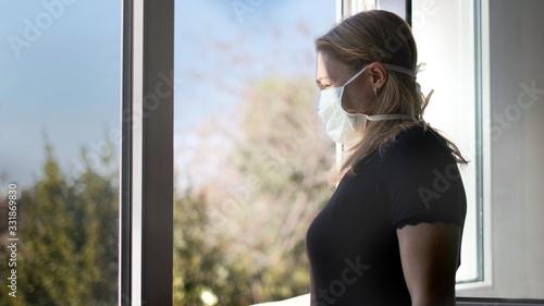 Fototapeta horizontal background of woman in isolation opening window taking fresh air against virus outbreak hypochondria obraz