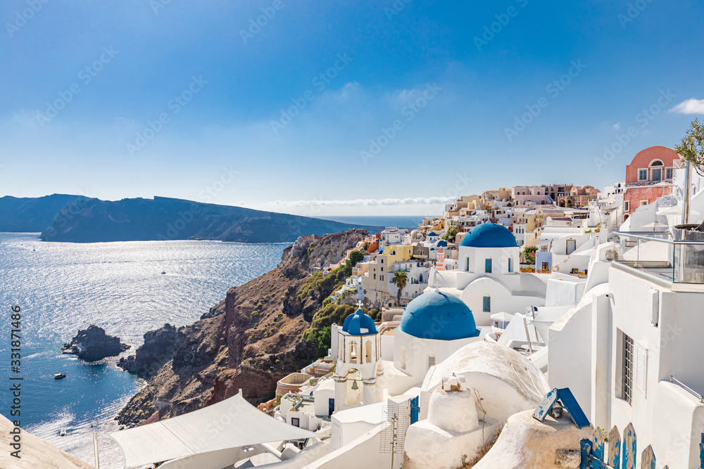 Fototapeta Amazing summer landscape, luxury vacation. Oia town on Santorini island, Greece. Traditional and famous houses and churches with blue domes over the Caldera, Aegean sea