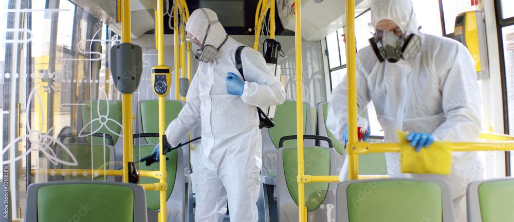 Fototapeta HazMat team in protective suits decontaminating public transport, bus interior during virus outbreak