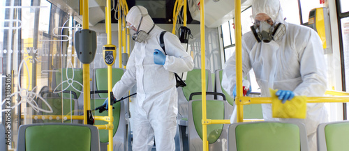 Canvastavla HazMat team in protective suits decontaminating public transport, bus interior d