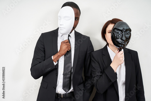 African man and Caucasian woman wearing black suits hiding face with plastic mas Canvas Print