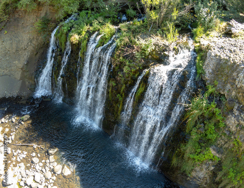 Awesome aerial shot of Upper Rock Creek Falls plunging over a rocky gorge into a pool of emerald water in Stevenson Washington State