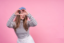 Young Cute Emotional Caucasian Lady In A Fashionable Beret Shows Heart On A Pink Background.
