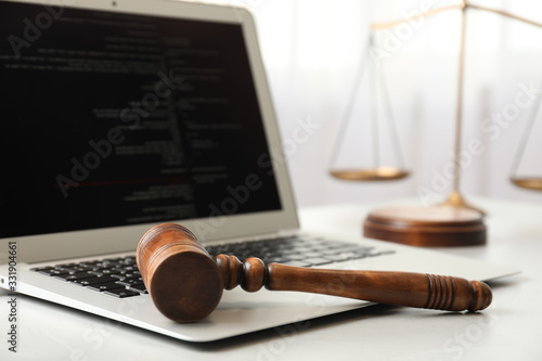 Photo Laptop, wooden gavel and scales on white table, closeup