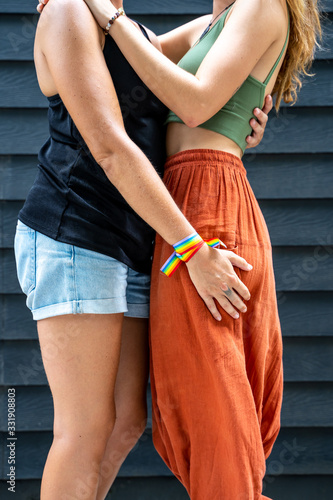 Fototapety, obrazy: Vertical photo of two young lesbian women hugging in the street