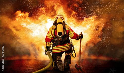 Feuerwehrmann kniet vor einem Feuer Fototapete