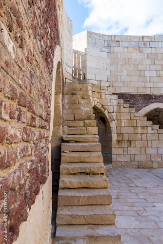 Exterior of ancient brick building with shabby stone stairway and crumbling arch Canvas Print