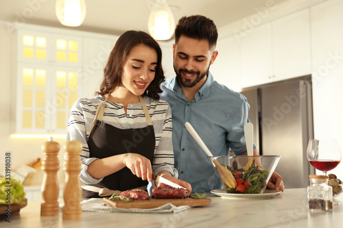 Fototapeta Lovely young couple cooking meat together in kitchen obraz