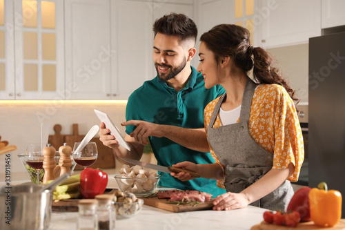 Foto Lovely young couple with tablet cooking together in kitchen