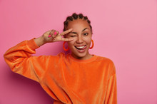 Portrait Of Cheerful Pretty Dark Skinned Female Enjoys Life, Makes Peace Sign With Fingers And Sticks Out Tongue, Enjoys Awesome Day, Event Or Party, Wears Vivid Orange Jumper, Winks Cheeky.