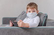 Quarantined children. Self isolation. A child in a medical mask with a smartphone playing games sitting on the couch.