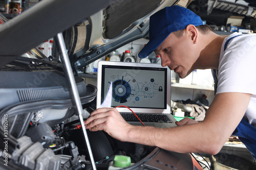 Fototapeta Mechanic with laptop doing car diagnostic at automobile repair shop obraz
