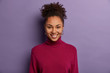 Portrait of happy smiling Afro American woman has joyful expression, glad to be promoted and receives praise from boss, wears casual turtleneck, isolated on purple background. Emotions concept