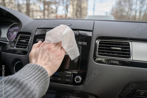 Fotografija Man cleaning front dashboard of a car using antivirus antibacterial wet wipe (napkin) for protect himself from bacteria and virus