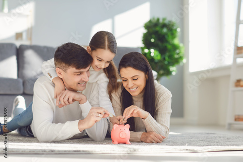 Canvas Print Happy family saves money in a piggy bank pig.