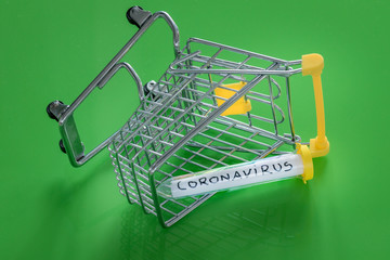 An overturned shopping trolley with a Coronavirus vial.  The concept of the negative impact of the virus on trade and the economy
