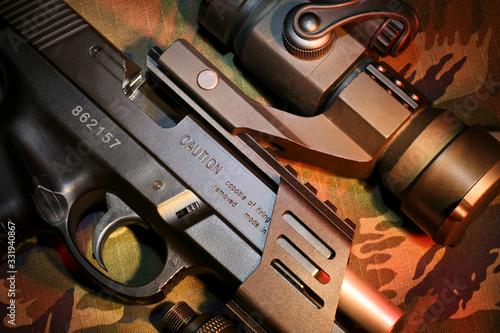 Detalhes de pistola de airsoft com mira acoplada no trilho em fundo camuflado Canvas Print