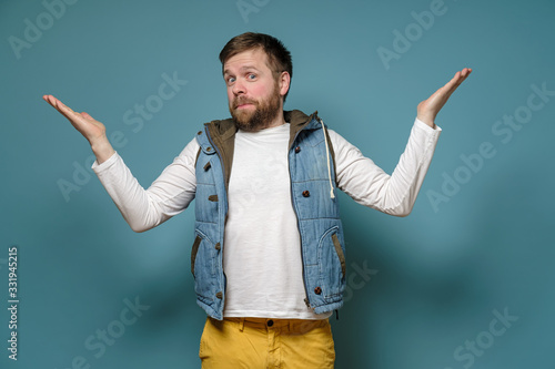 Caucasian bearded man looks guilty, he spreads arms to the sides and apologizes, on a blue background Fototapet