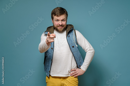 Cute bearded man points at someone with index finger and blames, smiles slyly and benevolent looks, on a blue background Wallpaper Mural