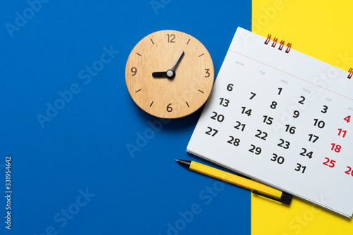 Cuadros en Lienzo close up of calendar and alarm clock on the blue and yellow table, planning for