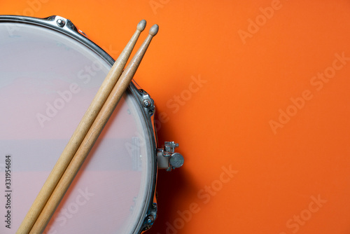 Cuadros en Lienzo Drum stick and drum on orange table background, top view, music concept