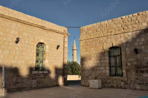 muslin walinkg toward a muezzon tower in jordan desert between houses Tablou Canvas