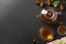 Beverage Of Mushroom Chaga In Glass Cup And Teapot On Black. Space For Text. Healthy Beverage. View From Above. Useful Coffee Alternative To Boost Immunity During The Coronavirus.