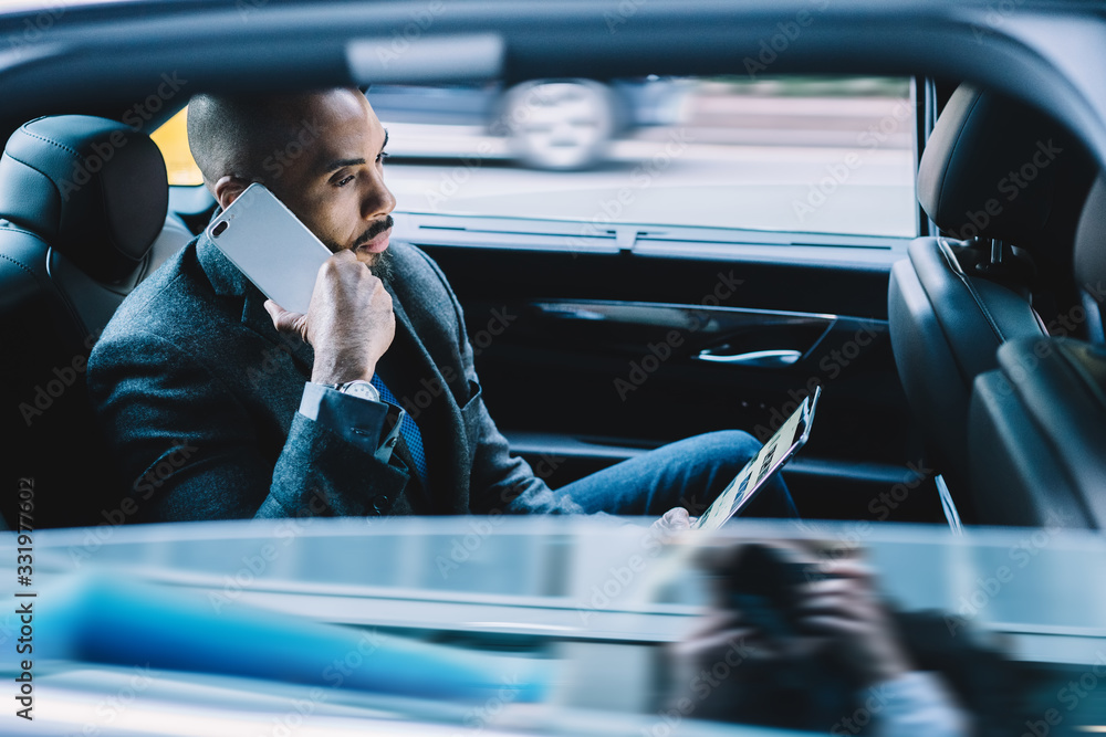 Fototapeta Focused ethnic male manager speaking on smartphone and using tablet in in car