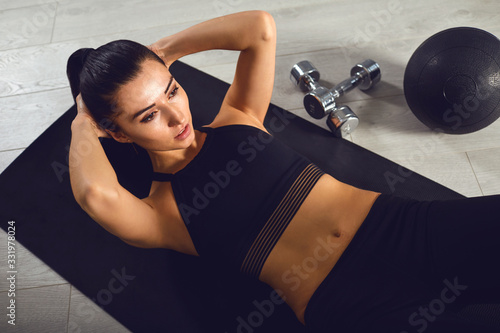 Fototapeta Exercises abs. Sporty girl in black sportswear doing abc exercises indoors. obraz