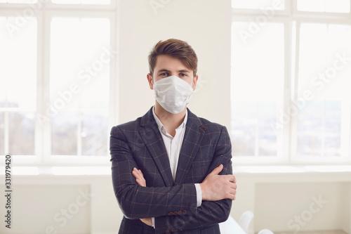 Obraz Danger of infection of the virus coronavirus infection. Businessman in medical mask at office - fototapety do salonu