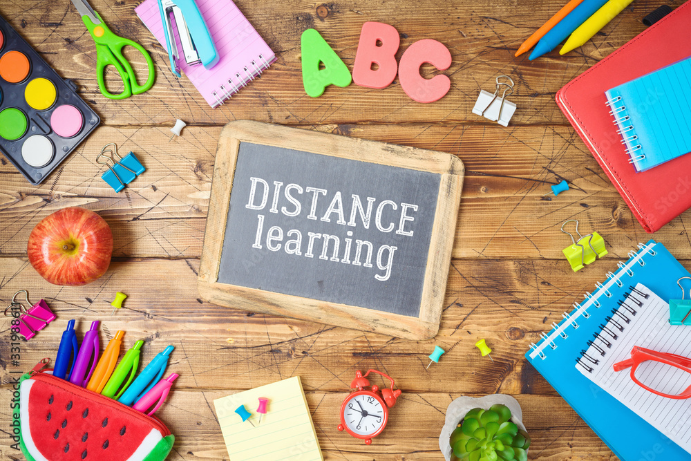 Fototapeta Distance learning and education concept. Study online from home with table and school supplies. Top view from above