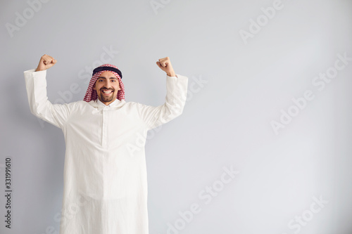 Photo Arab male businessman raised his hands up smiling standing on a gray background