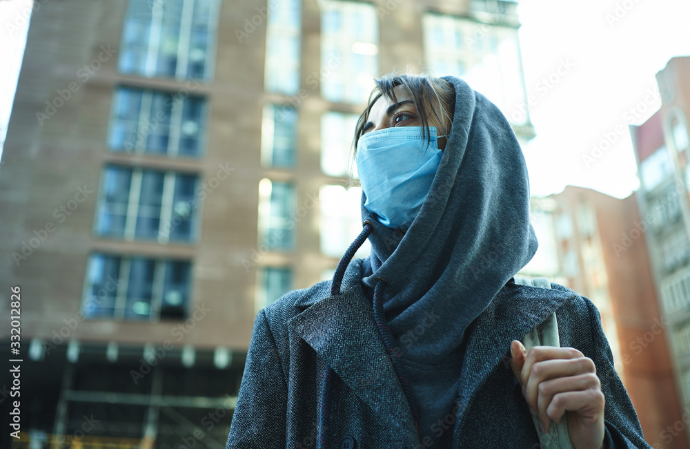 Fototapeta Woman in hood wearing protection face mask for prevention coronavirus, standing in city street with building on background.