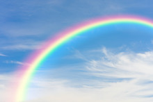 Rainbow And Blue Sky With Clouds Background