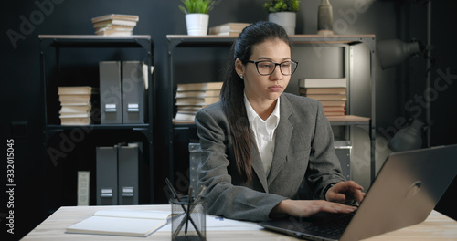 Fényképezés Young businesswoman in formal wear working on portable computer sitting at desk