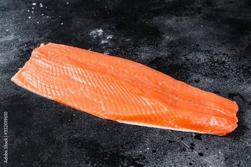 Fototapeta Raw salmon fillet. Organic fish. Black background. Top view. Copy space obraz