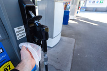A Mans Hand With A Disinfecting Wipe In It Holding A Gas Pump As A Precaution During The Coronavirus Pandemic 2020.