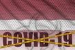 Latvia flag and Covid-19 inscription with orange quarantine border tape. Coronavirus or 2019-nCov virus concept