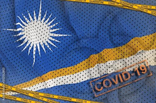 Fototapeta Marshall Islands flag and Covid-19 biohazard symbol with quarantine orange tape and stamp