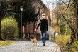 dog with  leash and owner with face mask walking outside