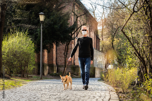 Fototapeta dog with  leash and owner with face mask walking outside obraz