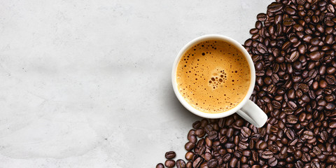 cup of coffee and bean on cement table background