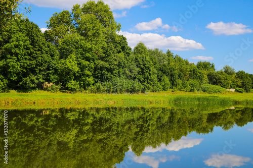 Fototapeta Reflection of trees and clouds in a lake or river. Sunny summer day. obraz na płótnie