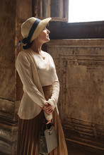 Woman In Hat Stands At A Windo...